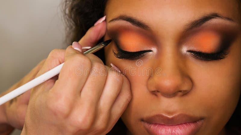 De make-upkunstenaar past make-up op gezicht van meisje toe stock foto's