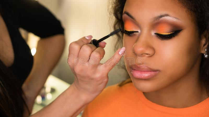 De make-upkunstenaar past make-up op gezicht van meisje toe stock afbeelding