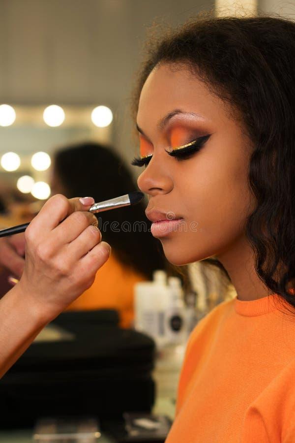 De make-upkunstenaar past make-up op gezicht van meisje toe royalty-vrije stock foto