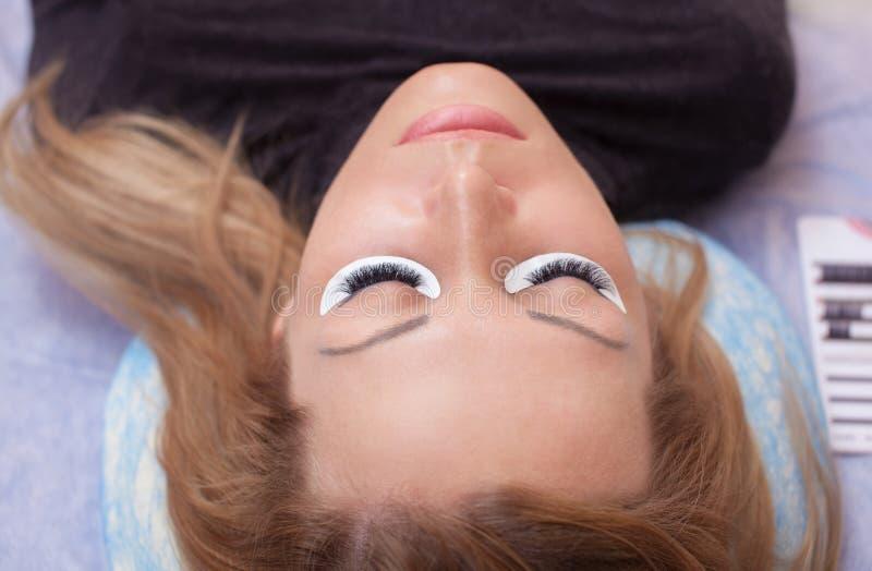 De make-upmeester verbetert, en versterkt wimpersstralen, standhoudend een paar pincet in een schoonheidssalon stock fotografie