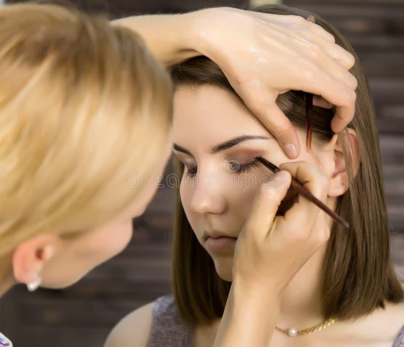 De make-upvrouw die van het oog oogschaduwpoeder toepast De stilist doet goedmaakt wijfje door eyeliner stock afbeeldingen