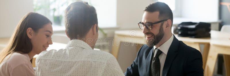 De makelaar in onroerend goed komt in agentschap met jong echtpaar samen stock afbeeldingen