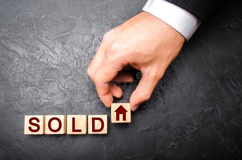 de makelaar in onroerend goed` s hand zet een kubus met een beeld van het huis aan het verkochte woord Concept het verkopen van e royalty-vrije stock foto's