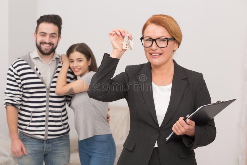 De makelaar in onroerend goed speelt met sleutels van nieuwe flat die door gelukkig jong paar wordt gehuurd royalty-vrije stock foto