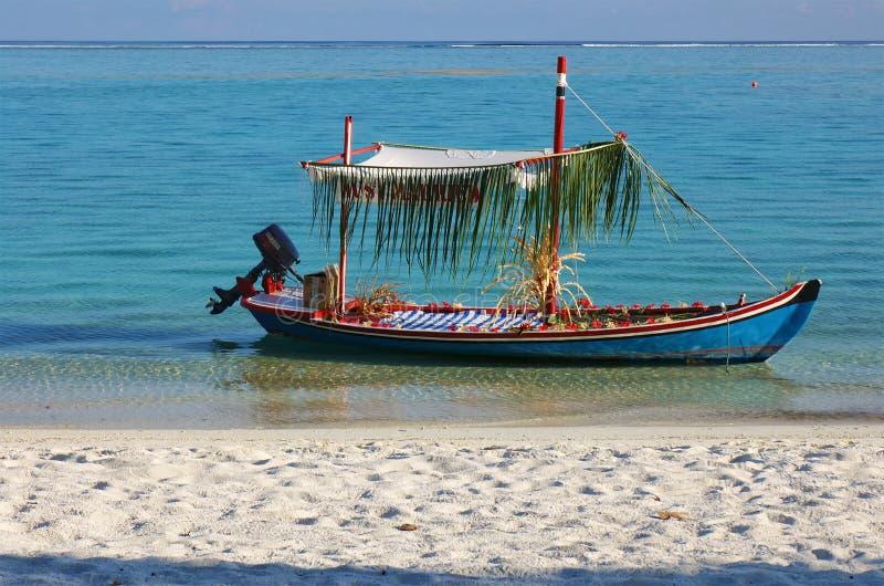 De Maldiven - Januari 18, 2013: De verfraaide boot van de huwelijksmotor met enkel Gehuwd die teken door zandig strand bij zonson royalty-vrije stock foto's