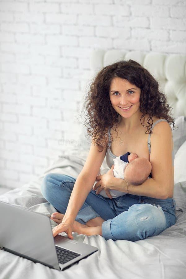 De mammawerken thuis met pasgeboren stock fotografie