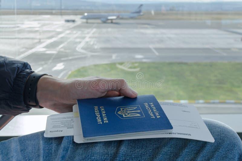 De Man'shand houdt Oekraïens buitenlands paspoort met kaartjes aan vliegtuig in achtergrond geparkeerd vliegtuig stock foto