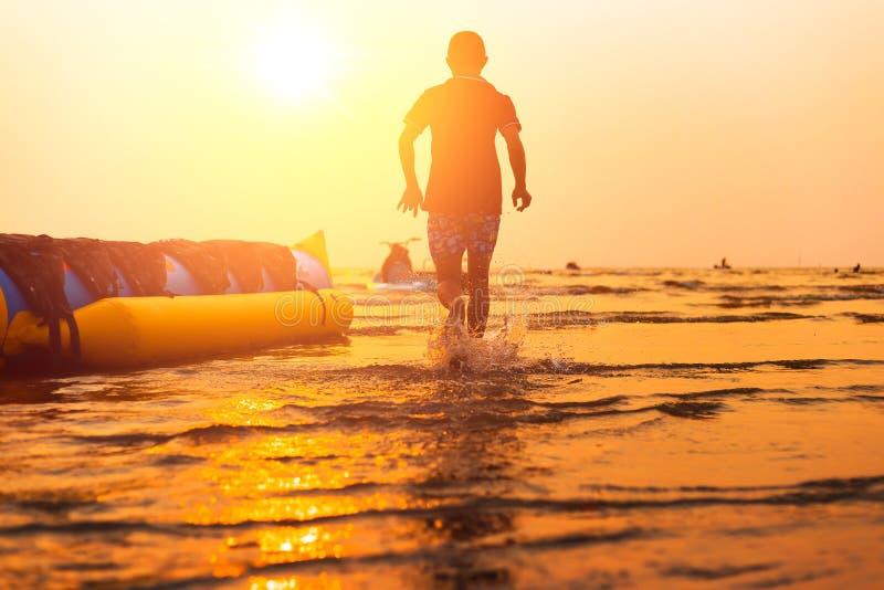 de man aan het overzees lopen en het water die bespatten royalty-vrije stock fotografie