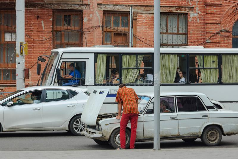 De man bevestigt de auto op de straat Echt straatgebeurtenis stock foto's