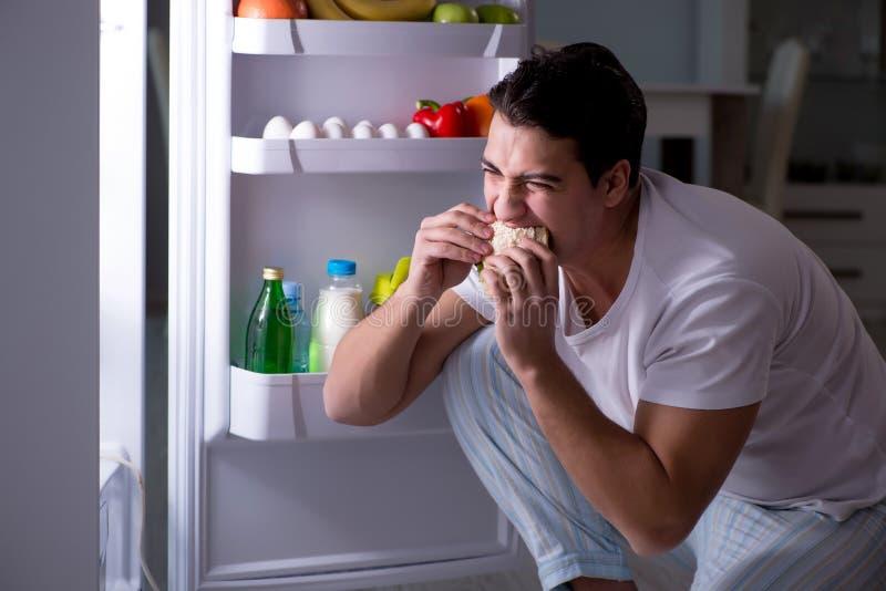 De man bij de koelkast die bij nacht eten stock foto