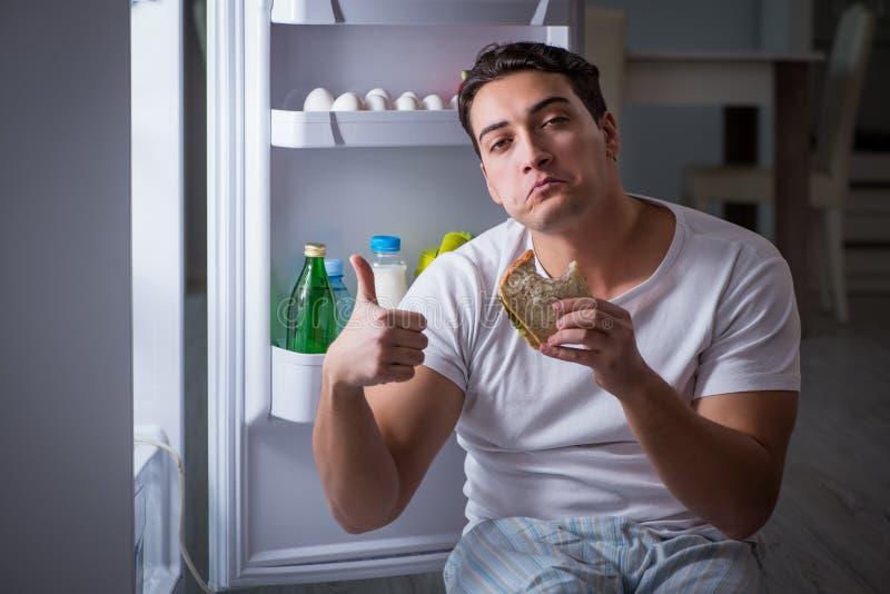 De man bij de koelkast die bij nacht eten stock fotografie