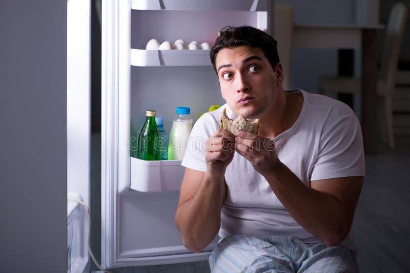 De man bij de koelkast die bij nacht eten stock foto's