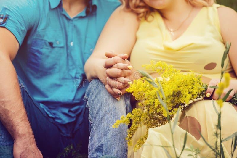 De man in blauwe kleren en de vrouw in gele kleding zitten stock foto's