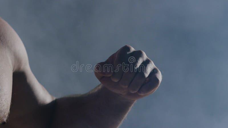De man in bokshandschoenen Jonge Bokservechter over zwarte achtergrond In dozen doende mens klaar te vechten Sterkte opleiding en stock foto