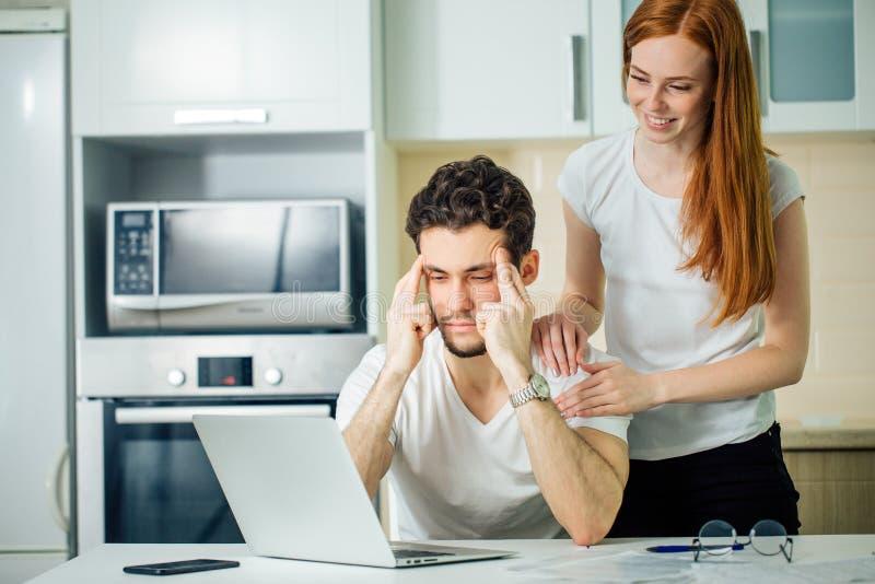 De man denkt met handen op zijn hoofd en zijn glimlachende vrouw gebruikend laptop stock afbeeldingen
