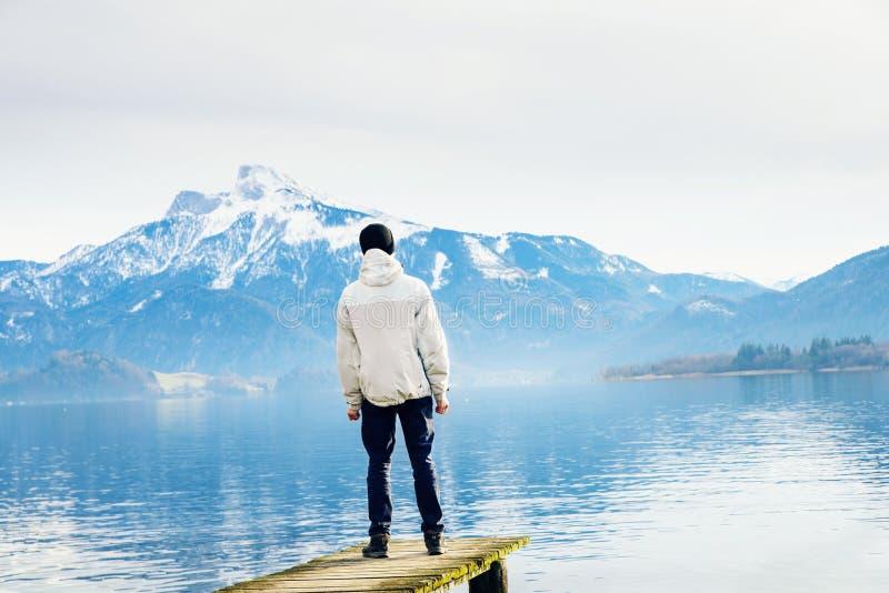 De man die het spiegelmeer en de bergen bekijken stock afbeeldingen