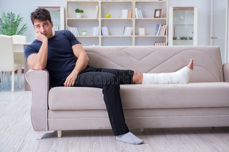 De man die met gebroken been thuis terugkrijgen stock fotografie