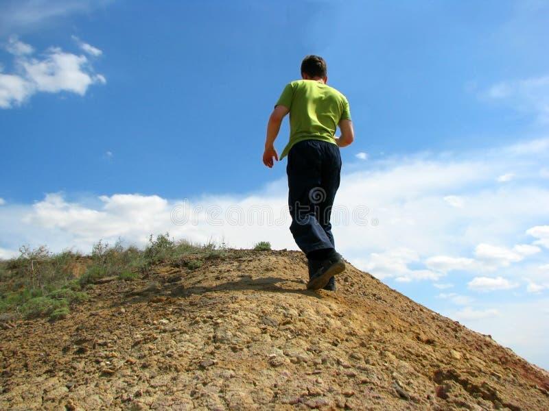 De man die op de heuvel beklimt stock afbeelding