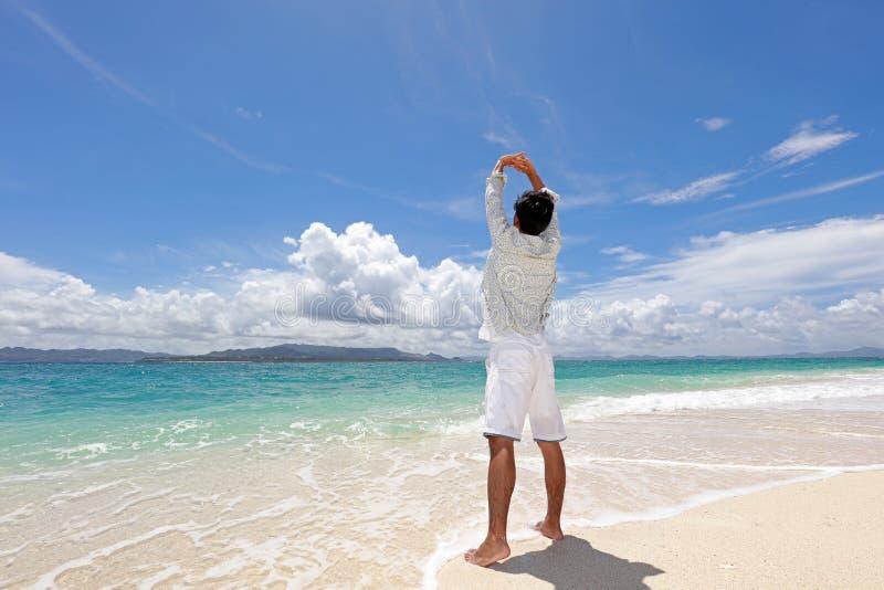 De man die op het strand ontspant stock afbeelding