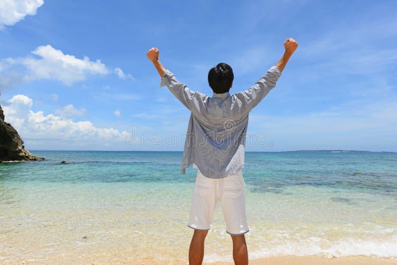 De man die op het strand ontspant stock fotografie
