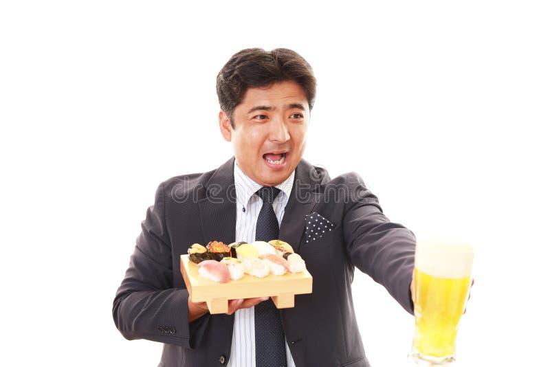 De man die sushi eet stock foto