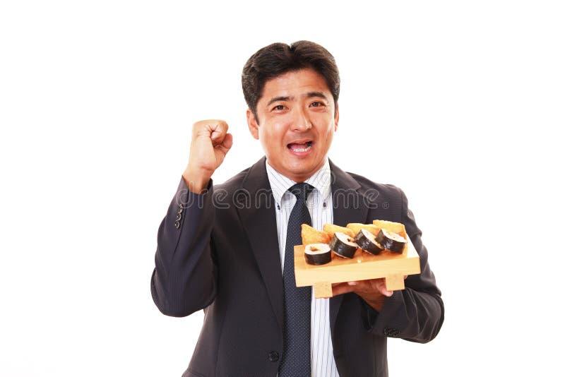 De man die sushi eet stock fotografie