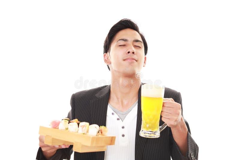 De man die sushi eet stock afbeelding