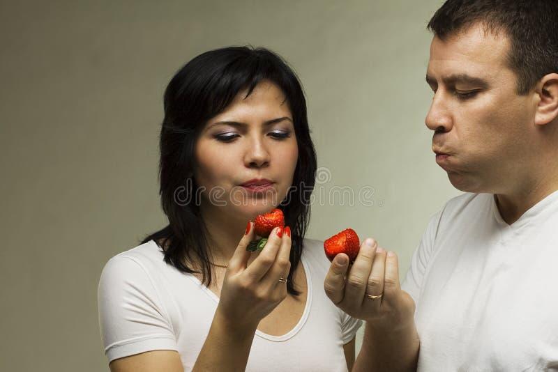 De man en de vrouw eten aardbei stock afbeelding
