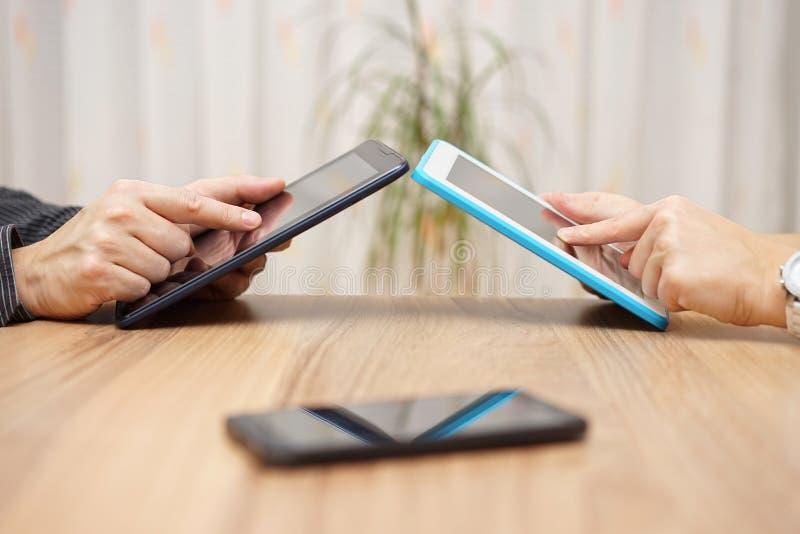 De man en de vrouw gebruiken tabletcomputers om muziek en gegevens te delen stock afbeelding