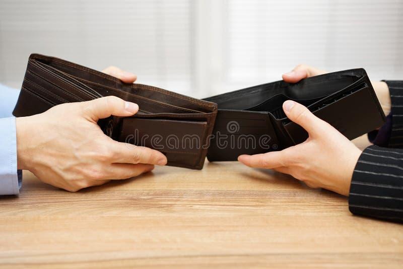 De man en de vrouw tonen lege portefeuille aan elkaar stock foto