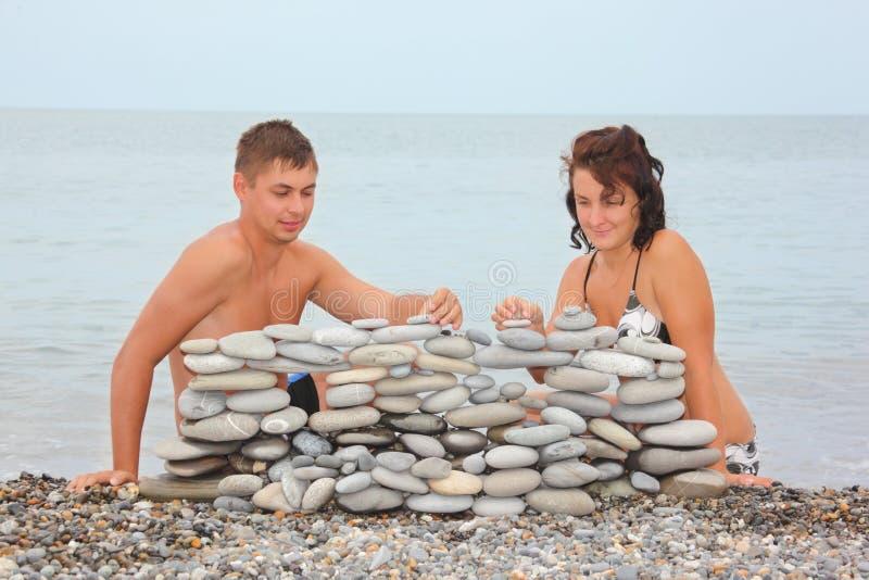 De man en de vrouw zijn bouwconstructie van kiezelstenen stock foto's