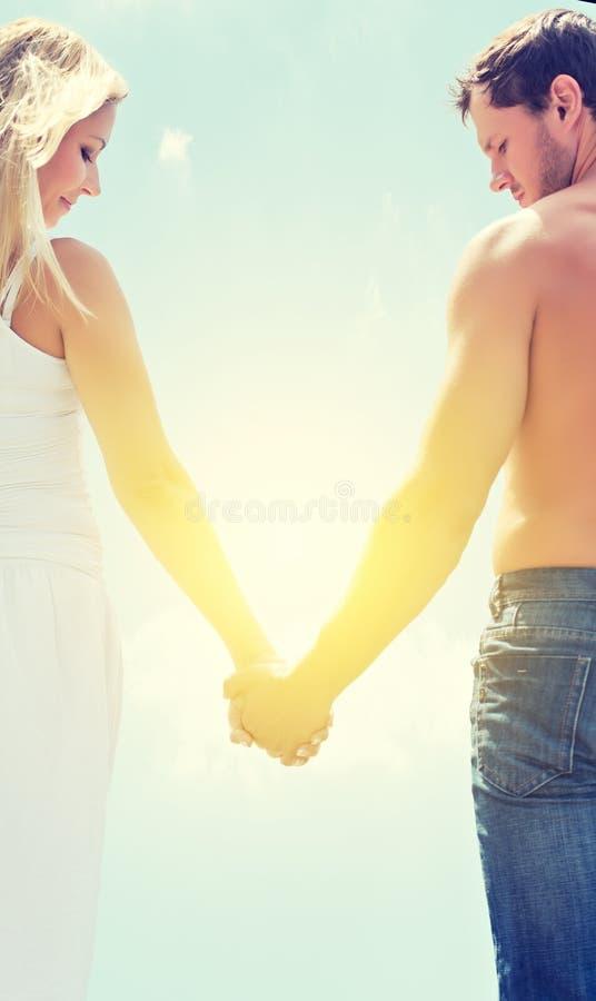 De man en de vrouwenholdingshanden van het liefdepaar op een hemel stock afbeelding