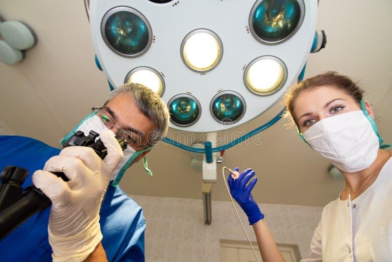De man en een vrouw in maskers bevinden zich onder ogen ziend elkaar en houdend medische instrumenten in hun handen stock afbeeldingen