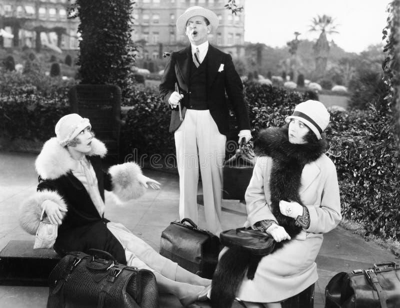 De man en twee die vrouwen liepen buiten in een tuin vast door bagage wordt omringd (Alle afgeschilderde personen langer ex leven stock afbeeldingen
