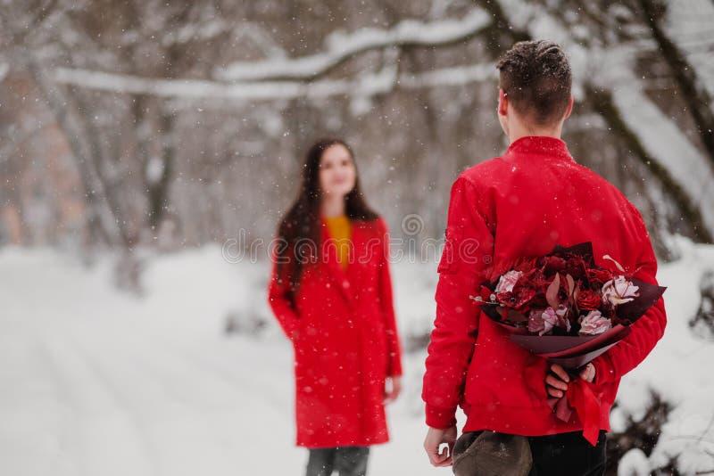 De man en de vrouw komen in snow-covered park in de winter samen De kerel verbergt achter een boeket van bloemen, een verrassing stock afbeelding