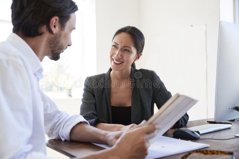 De man en de vrouw met documenten in een bureau, die sluiten omhoog glimlachen royalty-vrije stock foto's