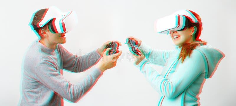 De man en de vrouw met virtuele werkelijkheidshoofdtelefoon spelen spel Beeld met glitch effect stock foto's