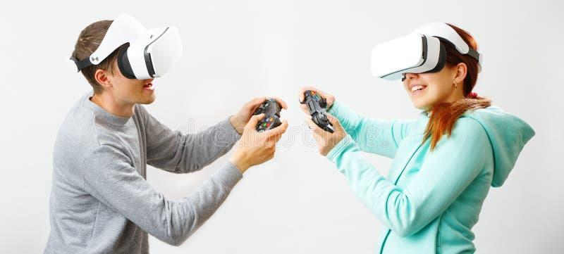 De man en de vrouw met virtuele werkelijkheidshoofdtelefoon spelen spel stock afbeeldingen