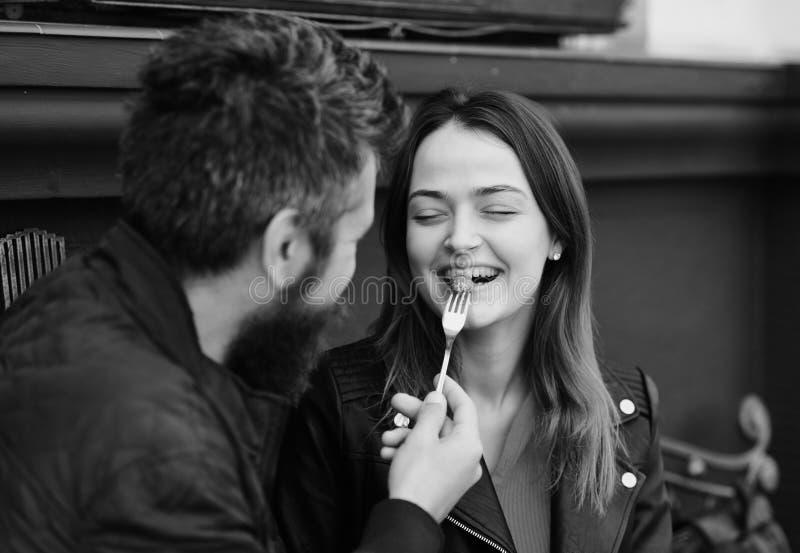 De man en de vrouw met vrolijk gezicht hebben datum bij koffie Het paar in liefde eet bessen Kerel met het meisje van het baardvo royalty-vrije stock foto's
