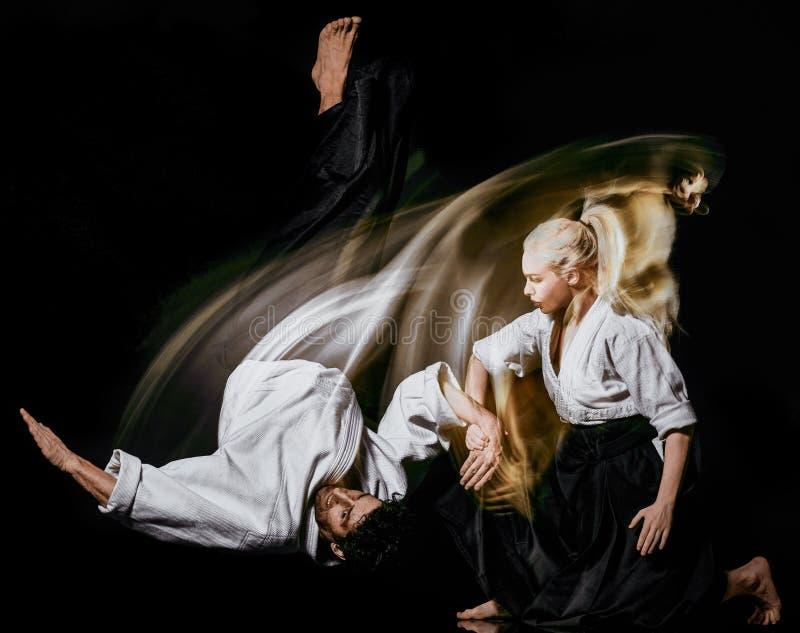 De man en de vrouw van Aikidobodokas isoleerden zwarte achtergrond stock fotografie