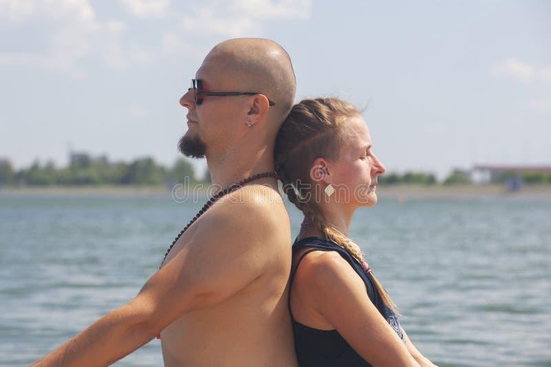 De man en de zwangere vrouw doen yoga op het strand stock foto's