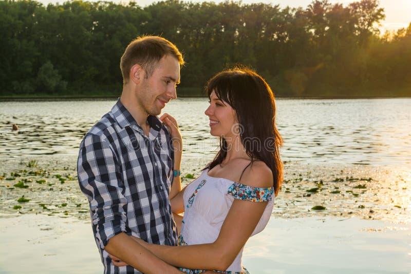 De man gaat de jonge vrouw kussen en koestert haar bij zonsondergang stock foto