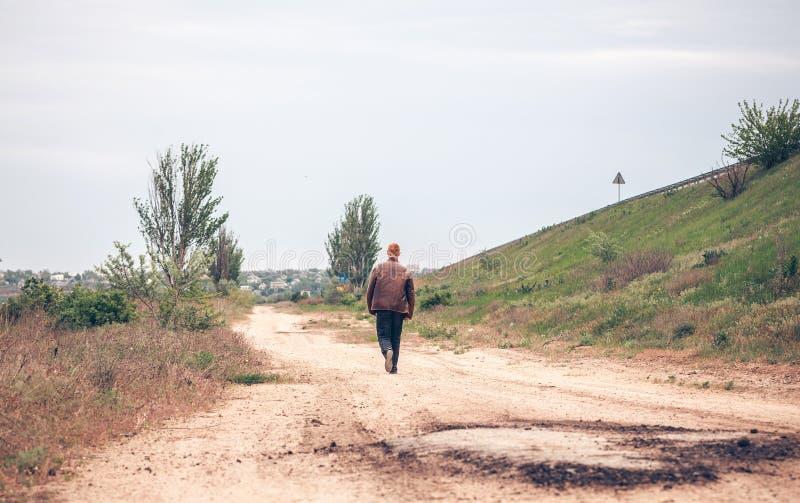 De man gaat op een landweg royalty-vrije stock foto's