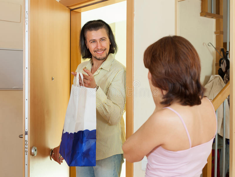 De man geeft een gift thuis aan vrouwen stock fotografie