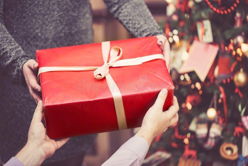 De man geeft een grote rode giftdoos aan een vrouw tegen de verbazende achtergrond van de Kerstmisboom Gestemde en selectieve nad stock foto's