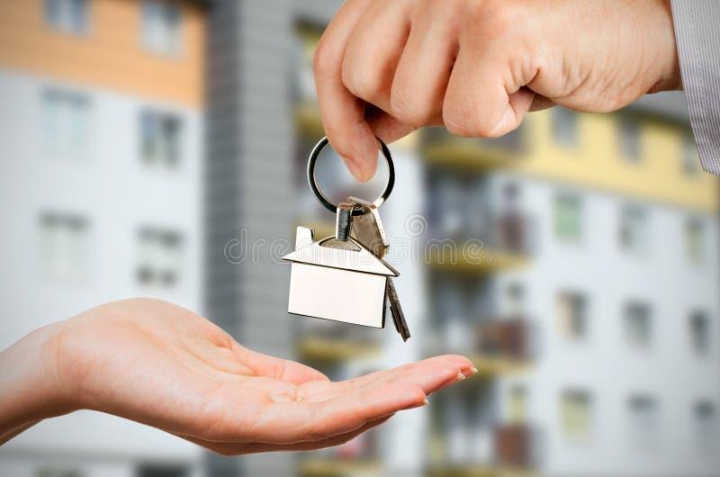De man geeft een vrouw de sleutels aan een nieuw huis stock fotografie