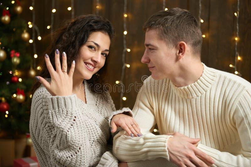 De man geeft het meisje een verlovingsring, paar in Kerstmislichten en decoratie, gekleed in wit, spar op donkere houten bedelaar stock afbeelding