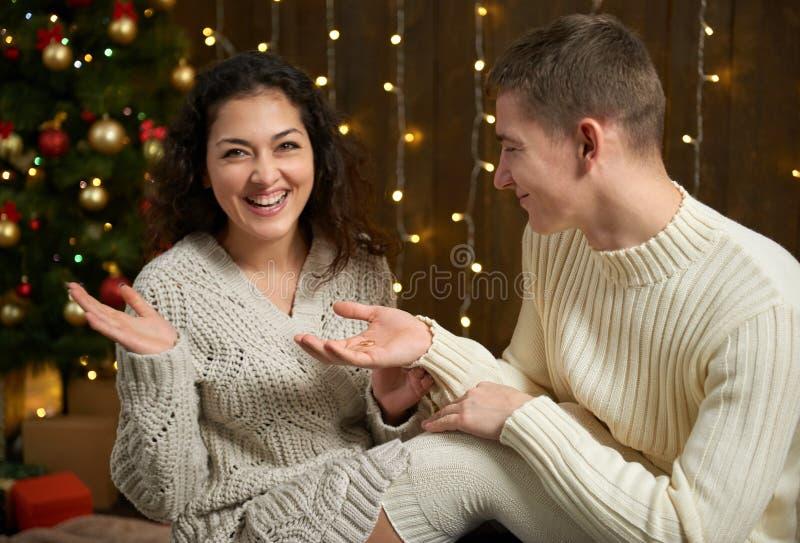 De man geeft het meisje een verlovingsring, paar in Kerstmislichten en decoratie, gekleed in wit, spar op donkere houten bedelaar royalty-vrije stock foto's