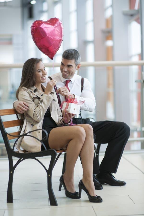 De man geeft vrouwengift en hart gevormde ballon stock fotografie