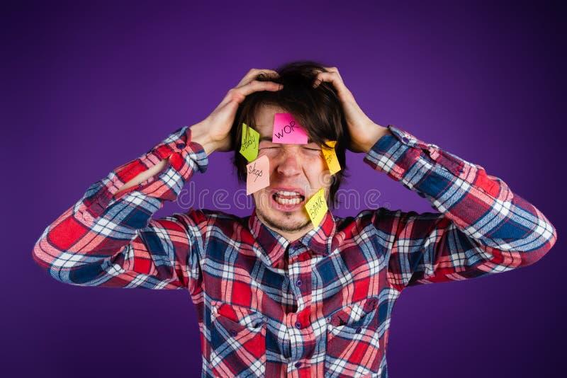 De man grijpt zijn hoofd en schreeuwen Een mens wordt geschokt door zijn verplichtingen en routine Stickers op gezicht met inschr royalty-vrije stock afbeelding